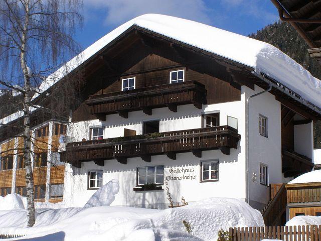 Ansicht nach Norden, unser Haus in einem tiefverschneiten Wintermantel und strahlendem Sonnenschein - Gaestehaus Obererlacher Obertilliach