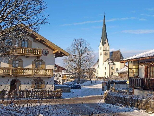 Der Sachsenkamer Dorfplatz mit der Pfarrkirche St. Andreas im Hintergrund im Winter - Sachsenkam Bayern