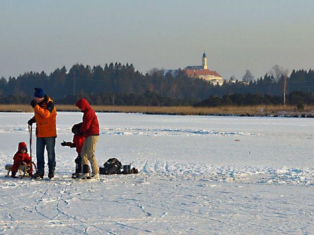 Der zugefrorene Kirchsee bietet jede Menge Spaß (Wandern, Schlittschuhlaufen, Eisstockschiessen) - Sachsenkam Bayern