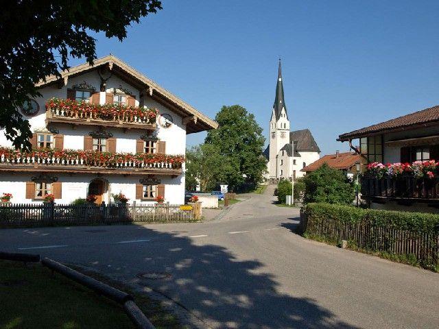 Der Sachsenkamer Dorfplatz mit der Pfarrkirche im Hintergrund - Sachsenkam Bayern